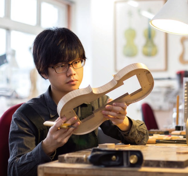 2018年度ヴァイオリン製作科のイメージ画像。製作途中の楽器の具合を確認する学院生