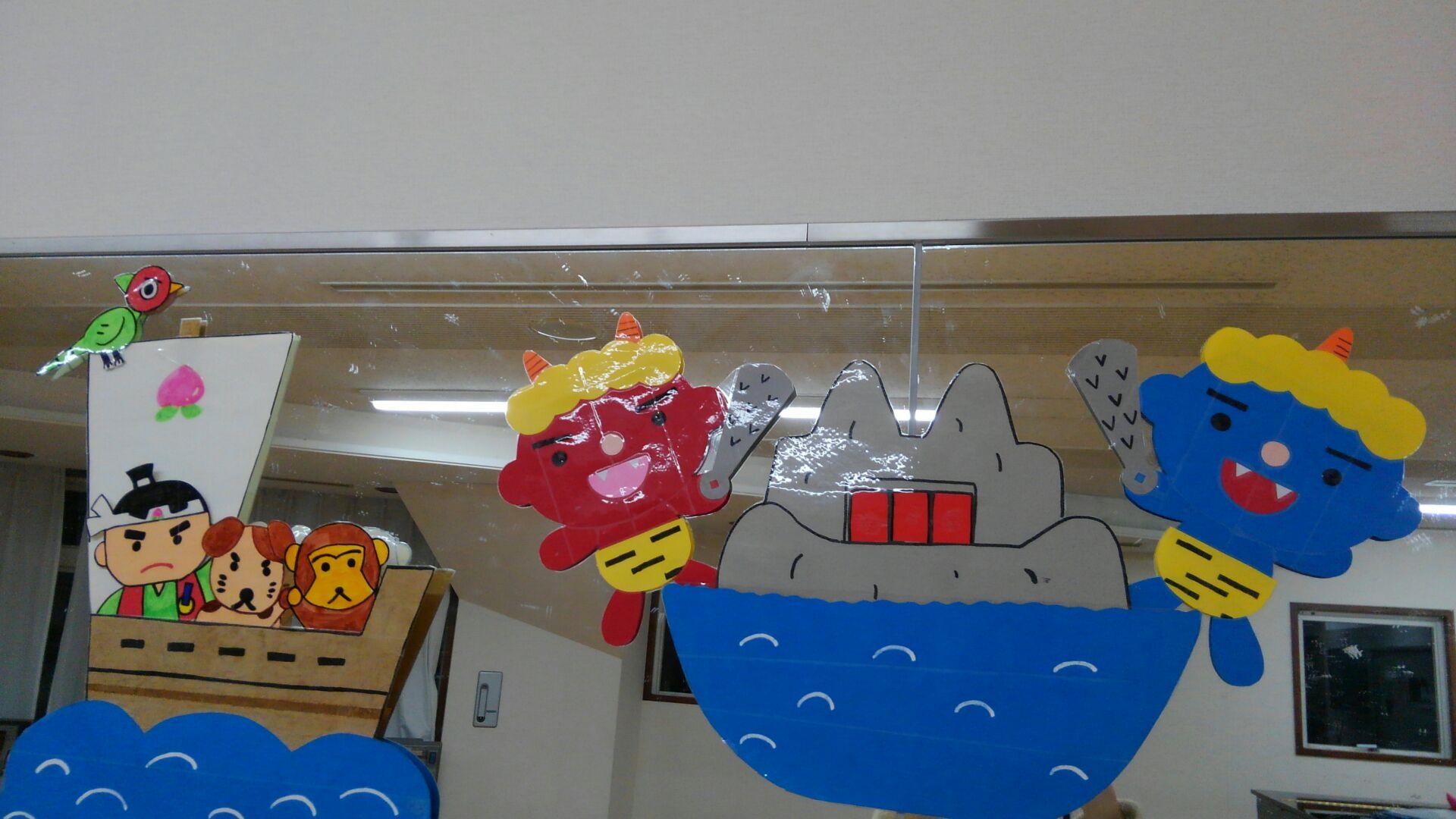 赤鬼と青鬼のいる鬼が島へ船で向かう桃太郎・猿・犬・きじ。