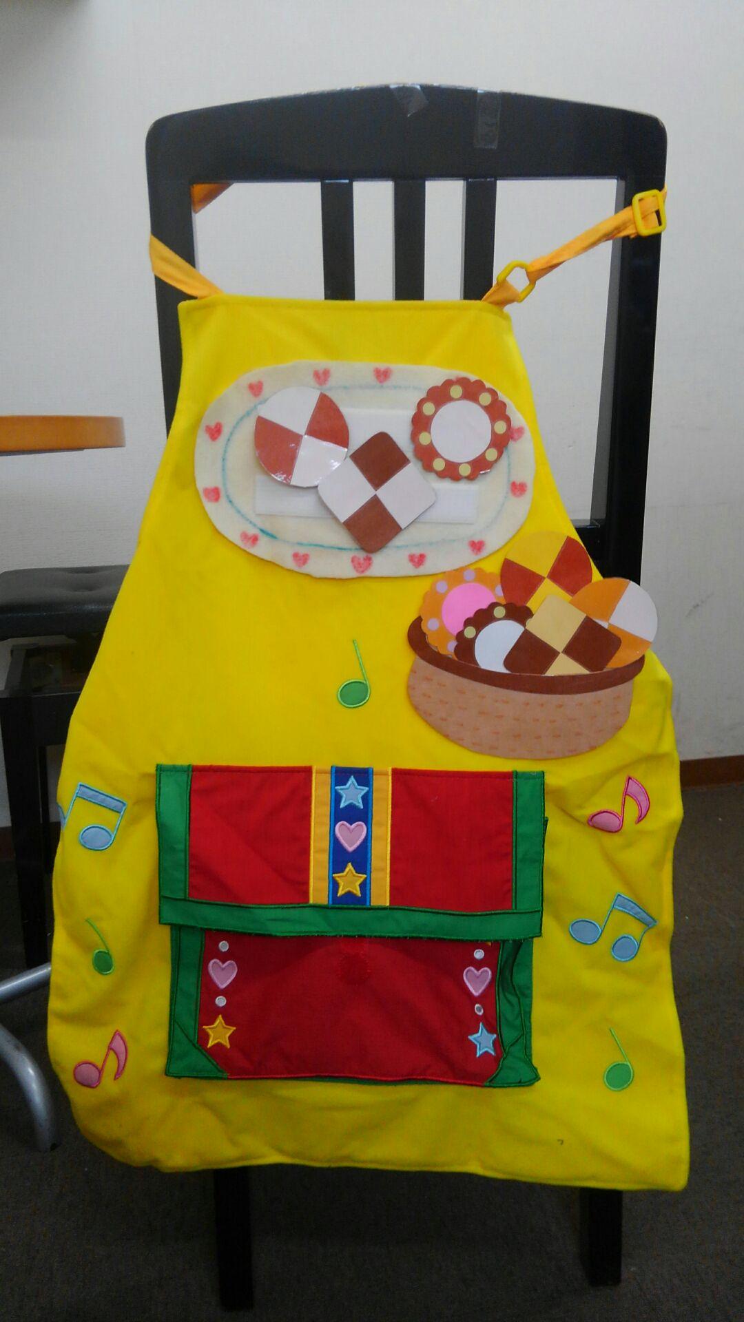黄色いエプロン。お皿やバスケットに盛られた様々なクッキー、音符、赤と緑を基調にしたポケットがあしらわれています。