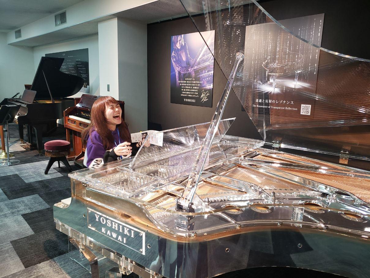 X JAPAN・YOSHIKIモデルのピアノに座り笑顔の女性学生